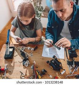 Father and daughter sitting by the wooden table and building robot at home as a school science project