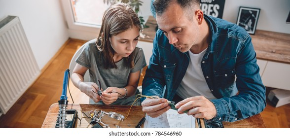 Father and daughter sitting by the wooden table holding circuit board and building robot at home as a school science project