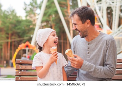 Father and daughter sitting on bench in the park, eating ice cream