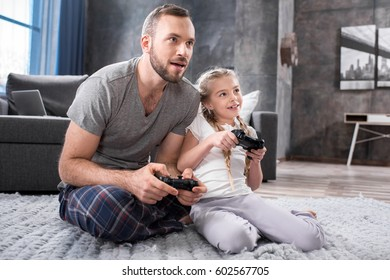 Father and daughter sitting on carpet and playing video games with joysticks