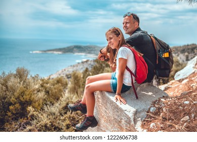 Father and daughter sitting on cliff's edge by the sea and looking into horizon