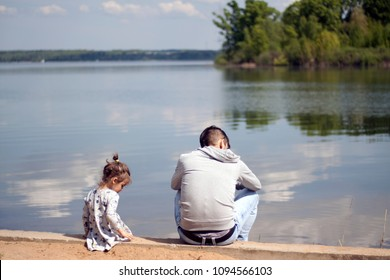 father and daughter are sitting on the lake