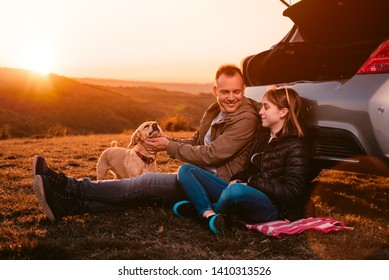 Father and daughter with small brown dog sitting by the car on the hill and enjoying sunset