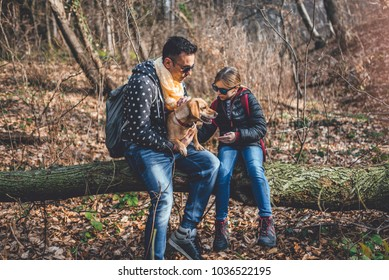 Father and daughter with a small yellow dog resting on the old tree log in the forest