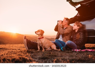Father and daughter with small yellow dog camping on a hill while sitting on the ground by the car and using binocular during sunset