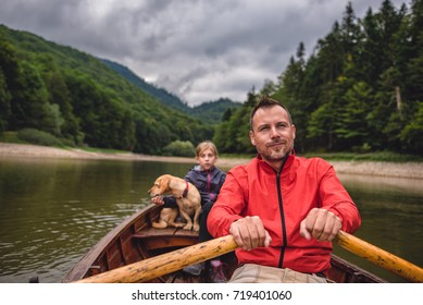 Father and daughter with a small yellow dog rowing a boat on a mountain lake