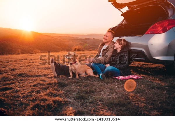 Father and daughter with small yellow dog camping on a hill while sitting on the ground by the car and having relaxing conversation