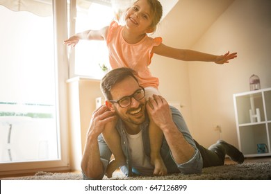 Father and daughter spending time at home. Little girl sitting on father shoulders. Looking at camera.