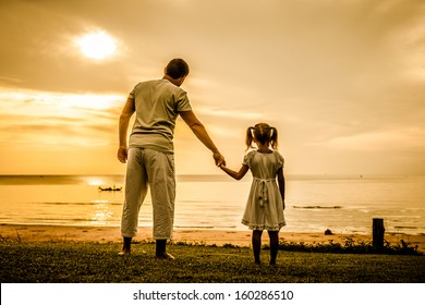 father and daughter standing at the beach in the dawn time
