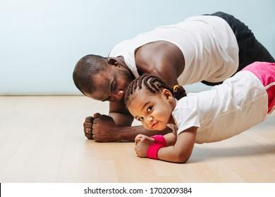 Vater und Tochter bleiben in Form in der Isolation zu Hause, und machen Planübung. Entwicklung ihrer Abs.