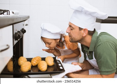 father with daughter  take some rolls on a baking tray  out of oven