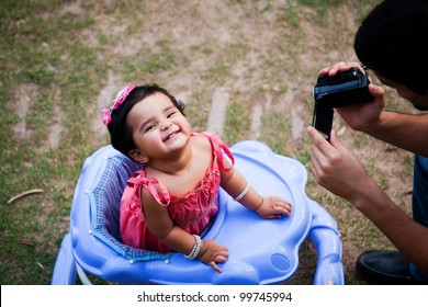 father and daughter, father taking pictures or making film of his daughter in sunny afternoon. man making film with handycam