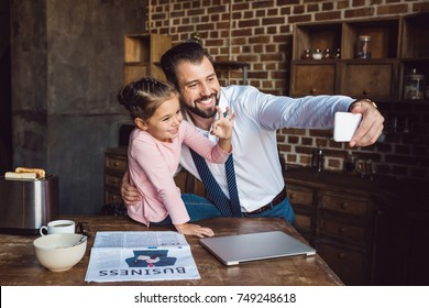 father and daughter taking selfie at kitchen in morning