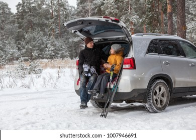 Father and daughter talking together after sports activities such as ski and ice skates. Sitting back trunk of suv at winter season