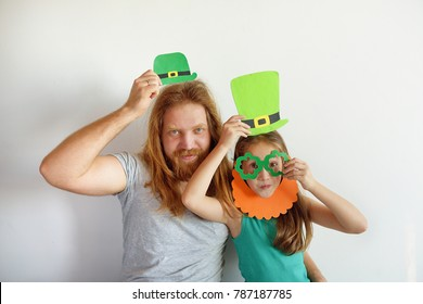 The father with the daughter try on masks for a St. Patrick's Day