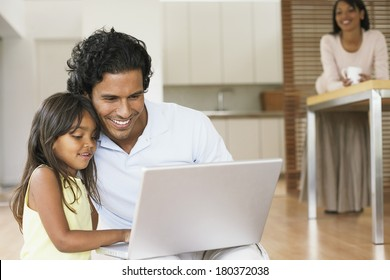 Father and daughter using laptop in kitchen.