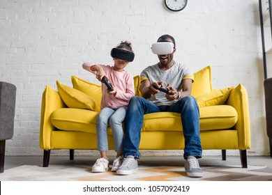 father and daughter in vr headsets playing video games on couch at home