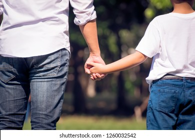 Father and daughter walking in the park holding hands. We will love and take care of you forever concept.