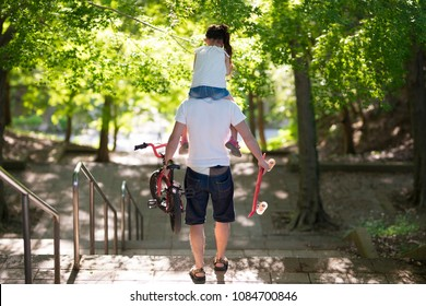 Father and daughter walking with a shoulder car