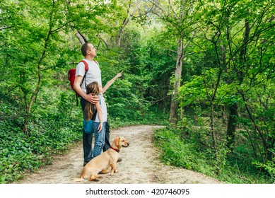 Father and daughter walking through the woods with dog.