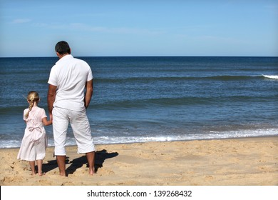 Father and daughter watching the horizon at the beach