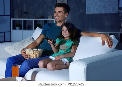 Father and daughter watching TV on sofa at night