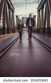 Father and daughter wearing black leather jacket walking across the freight bridge and talking