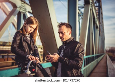 Father and daughter wearing black leather jacket relaxing on the freight bridge during sunset and using smart phone