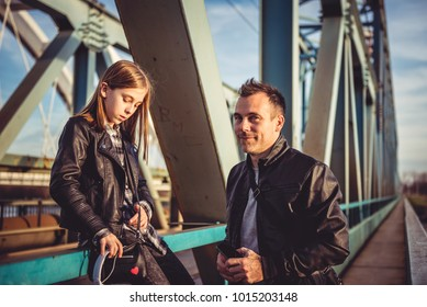 Father and daughter wearing black leather jacket relaxing on the freight bridge during sunset
