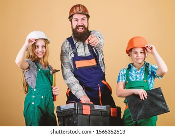 Father and daughter in workshop. Family teamwork. Repair. Repairman in uniform. Engineer. Bearded man with little girls. construction worker assistant. Builder or carpenter. Cheerful mechanic.