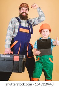 Father and daughter in workshop. Repair. Childrens creativity. Repairman in uniform. Engineer. Bearded man with little girl. construction worker assistant. Builder or carpenter. Making things perfect.
