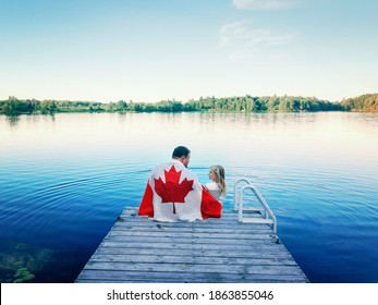 Father and daughter wrapped in large Canadian flag sitting on wooden pier by lake. Canada Day celebration outdoor. Dad and child sitting together on 1 of July celebrating national Canada Day.