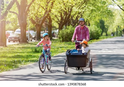Father and daughters having a ride with cargo bike during spring