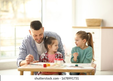 Father and daughters painting at table indoors. Playing with children