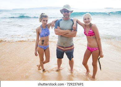 Father and Daughters playing together at the beach