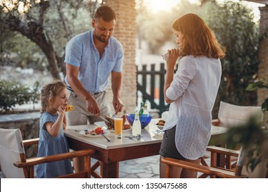 Father and dauther having mediterranean dinner on a terrace in a olive garden during summer vacation