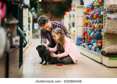 Father and dauther plays with puppy in pet shop