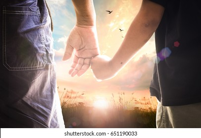 Father day concept: Son hand holding dad finger on meadow autumn sunrise background