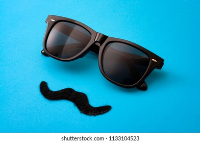 Father day and male hipster fashion concept with minimalist image of a pair of square sunglasses and a fake moustache on colorful blue background