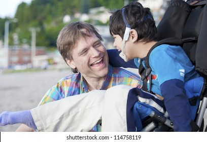 Father and disabled five year old son laughing together on beach