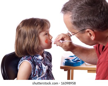 Father doing an halloween make-up to his daughter