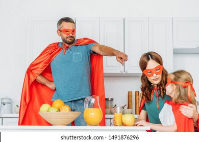 father dressed in superhero costume pointing with finger at daughter and wife sitting at kitchen table in superheroes costumes