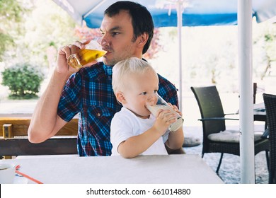 Father drinks beer, child drinks juice in a beach bar. Dad and son are best friends! Family spend time together in a cafe, restaurant in a summer day. Lifestyles, Family, Vacation concept.