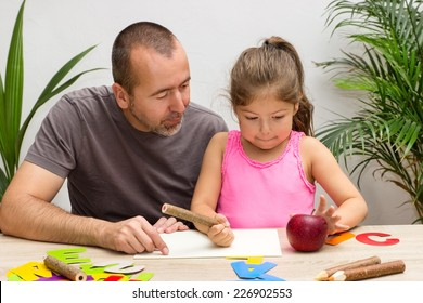 A father is exercising the alphabet with his little daughter