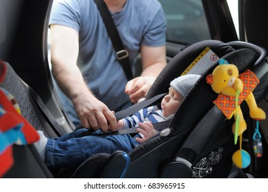 Father fasten his little son in car seat