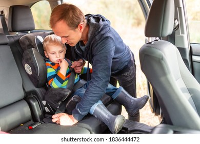 Father fastening safety belt for his baby boy in his car seat. Children's Car Seat Safety