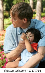 Father feeding baby a bottle in the park