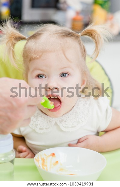 Father feeding cute baby daughter at home