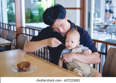 Father feeding food (bakery) to Cute little Asian 1 year old toddler baby boy child with spoon at the restaurant, Dad and son spending time together concept