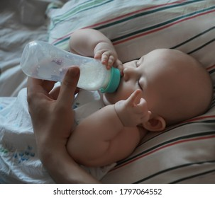 Father feeding his baby boy or daughter a bottle at home in the bedroom. fathers day idea.